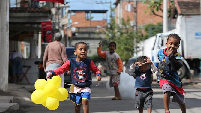 Children play in the Varginha area of the Manguinhos slum complex where Pope Francis visited the day before, in Rio de Janeiro, Brazil, Friday, July 26, 2013. Observers said that Varginha, which has four evangelical churches to the two Catholic ones, was strategically chosen as the site of Thursday's papal visit in a bid to help staunch tide of conversions in this key Catholic country. But while local residents Catholic and evangelical alike said that Francis' visit was a big success, bringing out an enthusiastic crowd of thousands despite a cold rain, they also said it would take more than his quick trip to slow the growth of the Pentecostal congregations. (AP Photo/Andre Penner)