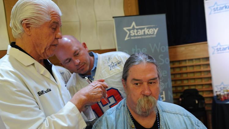 Bill Austin, founder of Starkey Hearing Foundation fits musician Owen Tufts with a new hearing aid on Saturday, Feb. 2, 2013 in New Orleans. (Photo by Cheryl Gerber/Invision for Starkey Hearing Foundation/AP Images)