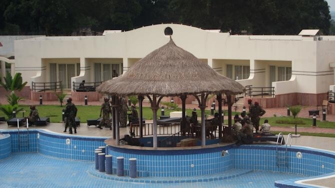 In this photo taken Thursday, April 4, 2013, rebel soldiers from the Seleka alliance, now controlling Central African Republic, stand guard in military fatigues around the pool at the Ledger Plaza Bangui Hotel in Bangui, Central African Republic. Rebel fighters seized the presidential palace when they overtook the capital in March, but when it came to setting up shop they set their sights a bit loftier: the city's sole luxury hotel. The hotel is now home to the top brass who sleep in rooms where executive suites start at $675, and the self-appointed president, whose luxury villa behind the drained swimming pool has a listed rate of about $3,850 a night. (AP Photo/Krista Larson)