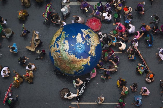 "Activists push an inflatable globe during a ""Global March"" as part of the People's Summit for Social and Environmental Justice in Defense of the Commons, a parallel event during the UN Conference on S"