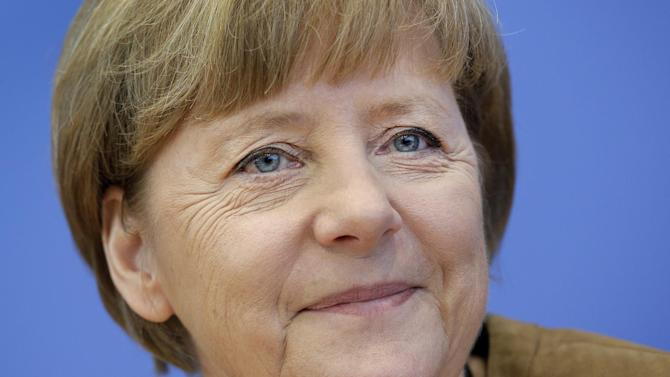 German Chancellor Angela Merkel smiles during her annual summer press conference in Berlin, Germany, Friday, July 18, 2014. (AP Photo/Michael Sohn)