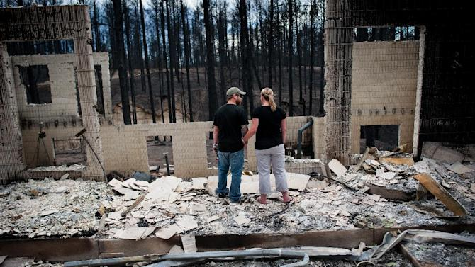 Jeremy and Kelly Beach look into the remains of their home off Ravine Drive, Tuesday, June 18, 2013, in Colorado Springs, Colo. Residents were allowed back into the area for a short period of time to view the properties that sustained the most damage from the fire. The Black Forest Fire, the most destructive wildfire in Colorado history, has destroyed 502 homes and charred more than 22 square miles. It was 85 percent contained Tuesday. (AP Photo/The Colorado Springs Gazette, Michael Ciaglo) MAGS OUT