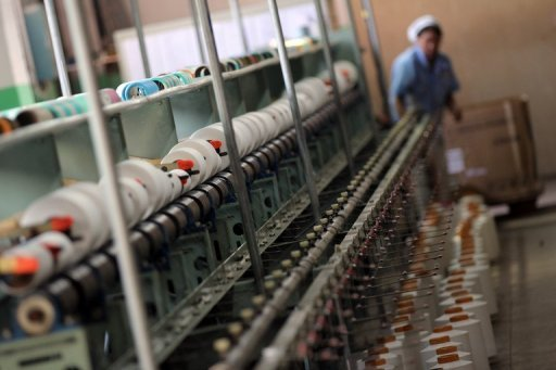 <p>A worker monitors a thread-making machine at a factory in Jinjiang, China's Fujian province. Production at China's factories, workshops and mines weakened in August, the government said Sunday, in a fresh sign of slowdown in the world's second-largest economy.</p>