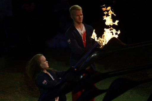 <p>Britain's swimmer Eleanor Simmonds (L) and sprinter Jonnie Peacock colllect the Paralympic flame as the cauldron unwinds for the final time during the closing ceremony of the London 2012 Paralympic Games at the Olympic Stadium in east London.</p>