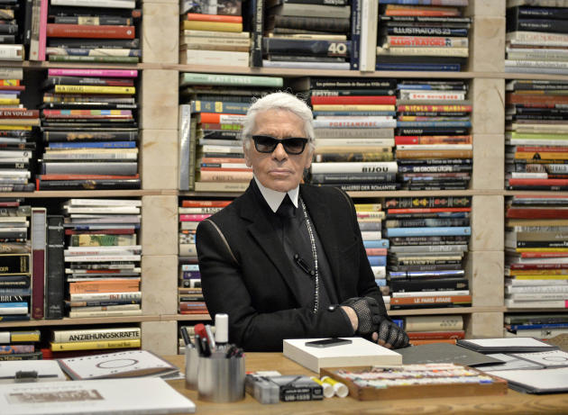 FILE - In this Feb. 14, 2014 file photo, fashion icon Karl Lagerfeld poses for photographers in front of his books prior to the start of an exhibition at the museum Folkwang in Essen, Germany. Lagerfe