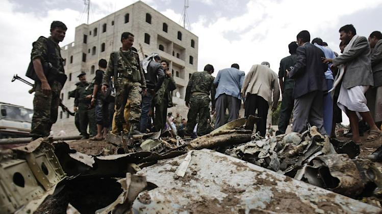 A plane wreck are seen on the ground as security forces and soldiers gather at the site of a plane crash in Sanaa, Yemen, Monday 13, 2013. A Yemeni military plane on a training exercise crashed Monday in the country's capital, slamming into a residential neighborhood and setting at least four houses ablaze. (AP Photo/Hani Mohammed)
