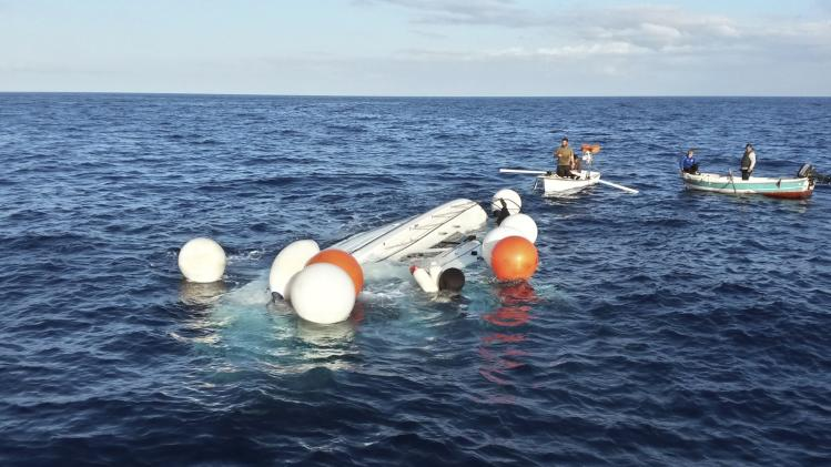 Crew members from a fishing boat look at a capsized vessel near Samos island, an eastern Aegean island close to border with Turkey