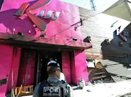 A policeman checks the Kiss nightclub where a blaze killed more than 230 people on January 28, 2013 in Brazil. An owner of the club tried to commit suicide, police said, as the number of survivors seeking medical treatment after the disaster continued to rise