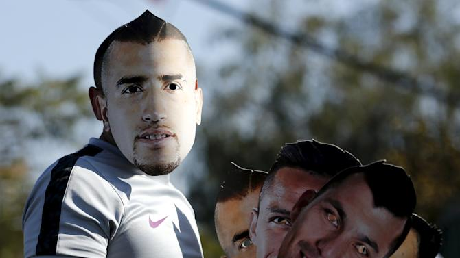 A Chilean soccer fan holds masks depicting soccer players ahead of the Copa America 2015 final soccer match between Chile and Argentina in Santiago