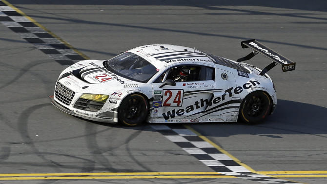 The WeatherTech Racing Audi R8 crosses the finish line to win the GT Class of the Grand-Am Series Rolex 24 hour auto race at Daytona International Speedway, Sunday, Jan. 27, 2013, in Daytona Beach, Fla. Filipe Albuquergue, Oliver Jarvis, Edoardo Mortara and Dion von Moltke were the drivers. (AP Photo/John Raoux)