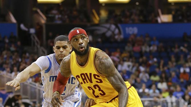 Cleveland Cavaliers' LeBron James (23) drives past Orlando Magic's Tobias Harris, left, during the first half of an NBA basketball game, Friday, Dec. 26, 2014, in Orlando, Fla. (AP Photo/John Raoux)