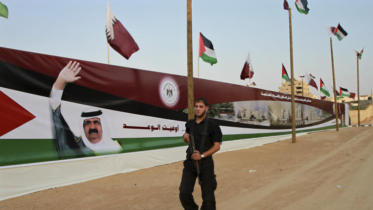 A Palestinain member of Hamas security forces passes by a mural of the Emir of Qatar Sheikh Hamad bin Khalifa al-Thani, in preparation for the upcoming visit to Gaza in Gaza City, Monday, Oct. 22, 2012. (AP Photo/Adel Hana)
