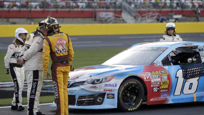 Kyle Busch, third from left, talks with NASCAR officials after a broken television camera cable damaged his race car during the NASCAR Sprint Cup series Coca-Cola 600 auto race at Charlotte Motor Speedway in Concord, N.C., Sunday, May 26, 2013. (AP Photo/Nell Redmond)