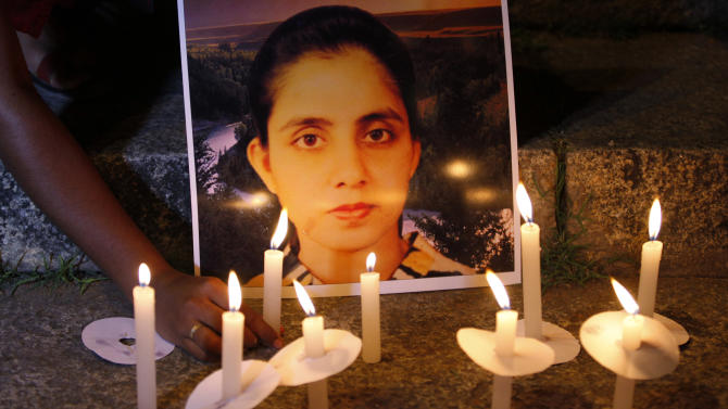 A student of a nursing college places a candle in front of a picture depicting nurse Jacintha Saldanha, during a candle-lit vigil organized by a local politician in Bangalore, India, Thursday, Dec. 13, 2012. An inquest into the apparent suicide of Saldanha, who was duped by a hoax call from Australian DJs about the pregnant Duchess of Cambridge, heard Thursday that she was found hanging in her room, had wrist injuries and left three notes. (AP Photo/Aijaz Rahi)