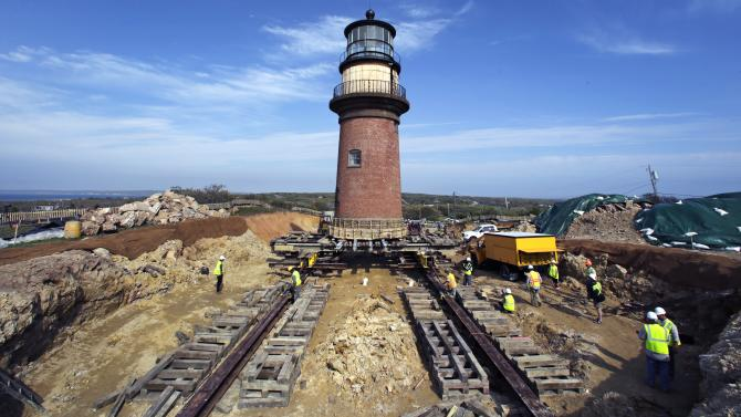 Workers move the Gay Head Lighthouse about 50 feet from its original footing (at center between the rails) in Aquinnah, Mass., on the island of Martha's Vineyard, Thursday, May 28, 2015. The 160-year-old lighthouse started its gradual 135-foot march to a new home slightly further inland. The $3.4 million effort to move and save the structure was due to fear that it could tumble down a rapidly-eroding cliffside. (AP Photo/Charles Krupa)