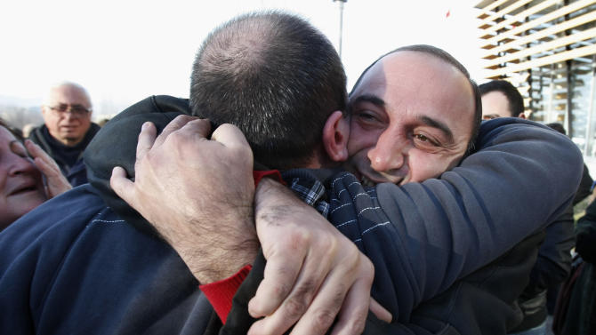 Relatives hug a former prisoner, back to camera, as he leaves Gldani prison No. 8 in Tbilisi, Georgia, Sunday, Jan. 13, 2013. Nearly 200 inmates considered political prisoners by Georgia's new parliament have walked free under an amnesty strongly opposed by President Mikhail Saakashvili. Many of those who walked free on Sunday were arrested during anti-Saakashvili protests in May 2011. Others had been convicted of trying to overthrow the government or of spying for Russia. (AP Photo/Shakh Aivazov)
