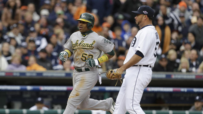 Oakland Athletics' Yoenis Cespedes scores in front of Detroit Tigers relief pitcher Joaquin Benoit from third on a wild pitch during the eighth inning of Game 2 of the American League division baseball series, Sunday, Oct. 7, 2012, in Detroit. (AP Photo/Paul Sancya)