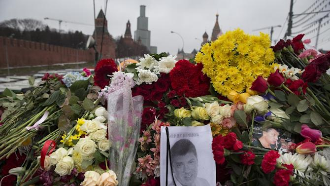Portraits and flowers are seen at the place where Boris Nemtsov, a charismatic Russian opposition leader and sharp critic of President Vladimir Putin, was gunned down on Friday, Feb. 27, 2015 near the Kremlin, with the Kremlin Wall is in the background in Moscow, Russia, Sunday, March 1, 2015. Russian investigators, politicians and political commentators on state television on Saturday covered much ground in looking for the reason Nemtsov was gunned down in the heart of Moscow, but they sidestepped one possibility, that he was murdered for his relentless opposition to Putin. (AP Photo/Pavel Golovkin)