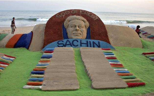 People walk past a sand sculpture of cricketer Sachin Tendulkar created by Indian sand artist Sudarshan Patnaik on a beach in Puri