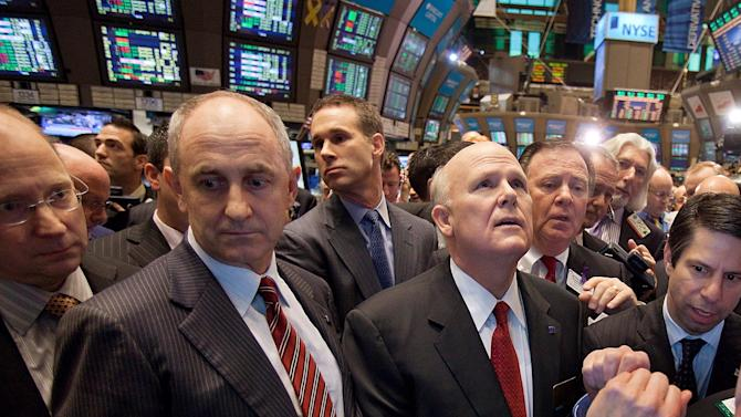 In this photo provided by NYSE Euronext, General Motors Co. CEO Daniel Akerson, center right, looks up at at the monitors that show trading activity at the GM post on the floor of the New York Stock Exchange Thursday, Nov. 18, 2010, in New York. General Motors stock began trading on Wall Street again Thursday, signaling the rebirth of an American corporate icon that collapsed into bankruptcy and was rescued with a $50 billion infusion from taxpayers. (AP Photo/NYSE Euronext, Ben Hider) NO SALES