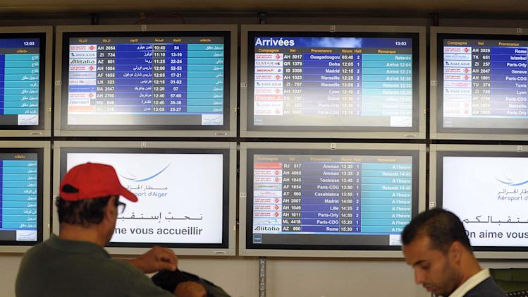 "People stand next to an arrival information screen showing the delayed Air Algerie flight 5017 at the Houari Boumediene airport near Algiers, Algeria, Thursday, July 24, 2014. An Air Algerie flight carrying 116 people from Burkina Faso to Algeria's capital disappeared from radar early Thursday over northern Mali and ""probably crashed"" according to the plane's owner and government officials in France and Burkina Faso. (AP Photo/Sidali Djarboub)"