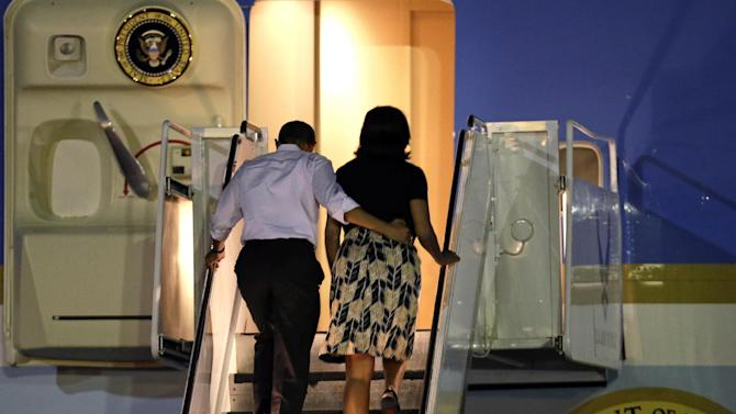 President Barack Obama and first lady Michelle Obama board Air Force One at Honolulu Joint Base Pearl Harbor-Hickam, Saturday, Jan. 5, 2013, in Honolulu, en route to Washington after their holiday vacation.  (AP Photo/Gerald Herbert)