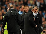 Manchester City's Italian manager Roberto Mancini (R) exchanges words with Manchester United manager Alex Ferguson (2nd R) during their English Premier League football match at The Etihad stadium in Manchester. City seized control of the Premier League title race after Vincent Kompany's first-half header powered them to a 1-0 win over bitter rivals United