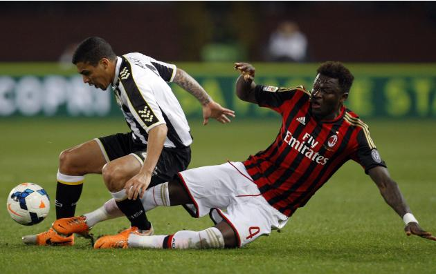 AC Milan's Muntari fights for the ball with Udinese's Loureiro during their Italian Serie A soccer match at Friuli stadium in Udine