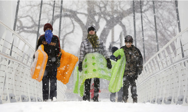 Chance Cain, from left, Simon Mourning and Nathan Talley walk towards a sledding hill near downtown Wichita, Kan. as a winter storm moves through the area on Monday, Feb. 25, 2013. (AP Photo/The Wichi
