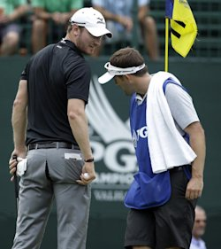 Chris Wood show a rip in his pants to his caddie on the 11th hole. (AP)