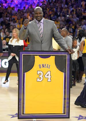 Former Los Angeles Lakers center Shaquille O'Neal stands with his retired jersey during the half of the Lakers'  NBA basketball game against the Dallas Mavericks, Tuesday, April 2, 2013, in Los Angeles. (AP Photo/Mark J. Terrill)