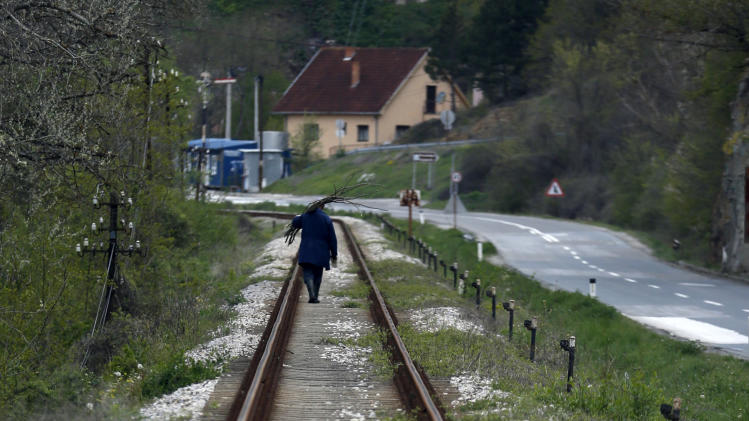 A man carries firewood on a rail track in the village of Rudnica, 280 kilometers south of Belgrade, Serbia, Thursday, April 17, 2014. (AP Photo/Darko Vojinovic)