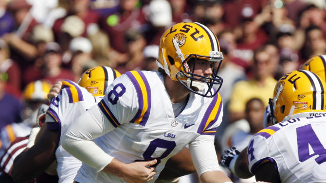 """FILE - In this Oct. 20, 2012, file photo, LSU quarterback Zach Mettenberger (8) hands off against Texas A&M during the first half of an NCAA college football game in College Station, Texas. Game manager sounds like such a mundane description for the quarterback of a national title contender. Yet Nick Saban, the coach of No. 1 Alabama, thinks it's the """"ultimate compliment"""" for AJ McCarron or for his counterpart Mettenberger of No. 5 LSU. (AP Photo/Eric Kayne, File)"""