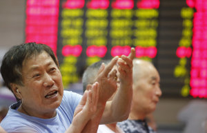 An investor gestures in front of the stock price monitor…