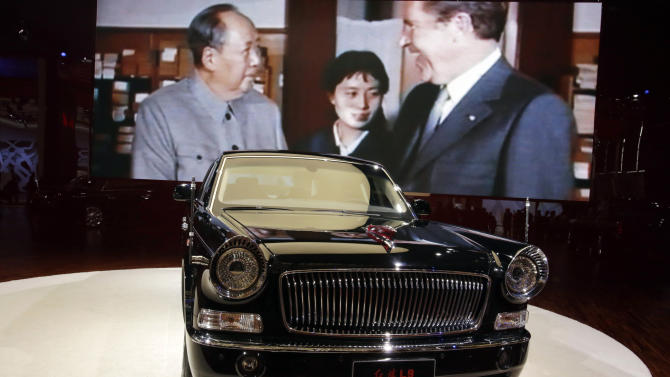 In this April 21, 2013 photo, the top of the line Hong Qi L9 is displayed near an image of then Chinese leader Mao Zedong meeting then U.S. President Richard Nixon at the Shanghai International Automobile Industry Exhibition (AUTO Shanghai) in Shanghai, China. China is reviving the illustrious Red Flag marque, better known at home by its Chinese name, Hong Qi, courtesy of a government-backed program to promote domestic brands that dovetails neatly with efforts to step-up China's diplomatic profile, partly through a greater emphasis on the pomp and circumstance accompanying state visits. The L9, is reserved for Chinese state leaders, flaunts a 6.4-meter (21-foot) armored chassis, suicide doors that open backward, and a price tag reported at around $1 million. (AP Photo/Eugene Hoshiko)