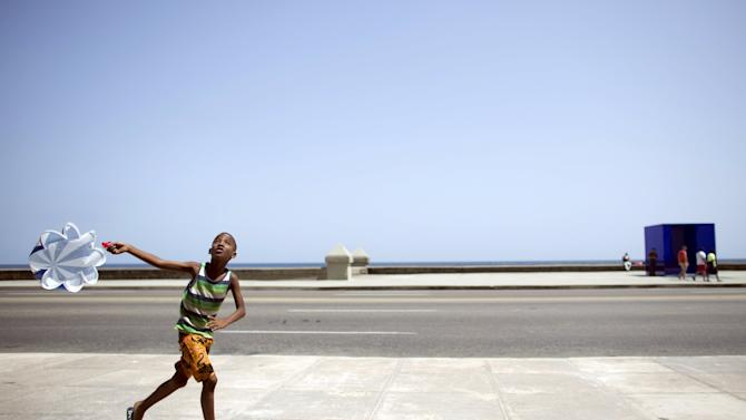 A boy plays with a parachute at the sea front Malecon in Havana
