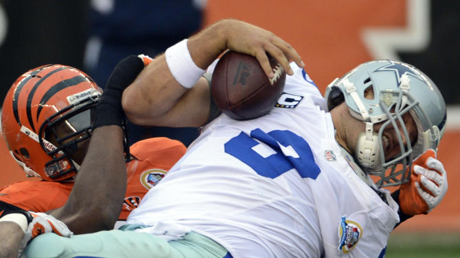 Dallas Cowboys quarterback Tony Romo (9) is sacked by Cincinnati Bengals defensive ends Carlos Dunlap and Michael Johnson in the first half of an NFL football game, Sunday, Dec. 9, 2012, in Cincinnati. (AP Photo/Michael Keating)