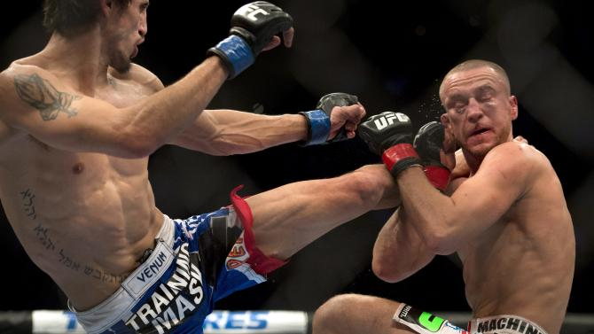 Mark Hominick, right, from Thamesford, Ont. takes a kick to the head from Pablo Garcia, from Fargo, ND, during their UFC Featherweight fight Saturday, Nov. 17, 2012 in Montreal. Garcia won with an unanimous decision. (AP Photo/The Canadian  Press, Ryan Remiorz)