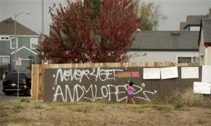 A girl reads signs in a vacant lot where 13-year-old Andy Lopez Cruz was shot and killed by sheriff's deputies on Tuesday in Santa Rosa