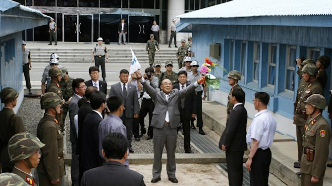 "Activist No Su-hui, center, shouts  ""Long Live Reunification""  in front of North Korean officials and soldiers, foreground, before crossing the demarcation line between North and South Korea where South Korean officials, at rear, were waiting for him, at the Demilitarized Zone at Panmunjom, Korea, on Thursday, July 5, 2012. South Korean officials immediately detained the activist for making an extended trip to Pyongyang without South Korean government approval as required by law. (AP Photo/Kim Kwang Hyon)"