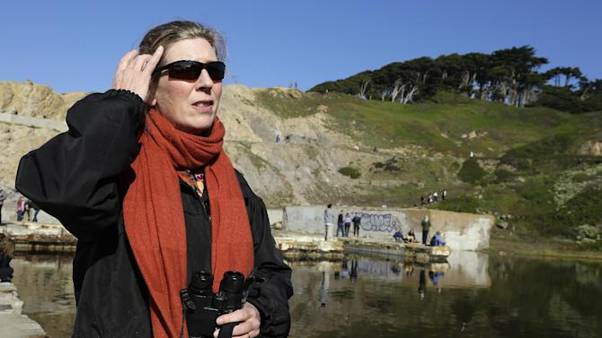 Megan Isadore, co-founder of the River Otter Ecology Project, waits for a glimpse of a river otter Thursday, Jan. 3, 2013, in San Francisco. For the first time in decades, a river otter has made San Francisco its home, taking up residence in the ruins of the Sutro baths, a 19th century seaside public pool facing the Pacific Ocean. (AP Photo/Ben Margot)