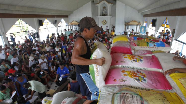 A worker lifts a sack of rice for distribution to the victims of super typhoon Haiyan inside a Catholic church at Tanuan