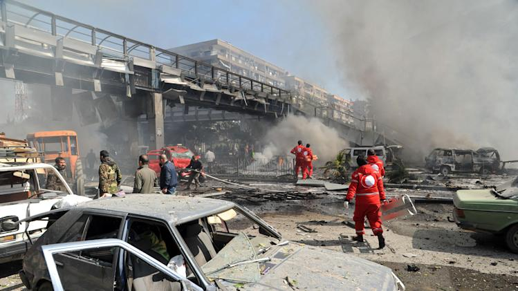 This photo released by the Syrian official news agency SANA, shows first responders working after a huge explosion that shook central Damascus, Syria, Thursday, Feb. 21, 2013. A car bomb shook central Damascus on Thursday, exploding near the headquarters of the ruling Baath party and the Russian Embassy, eyewitnesses and opposition activists said. (AP Photo/SANA)
