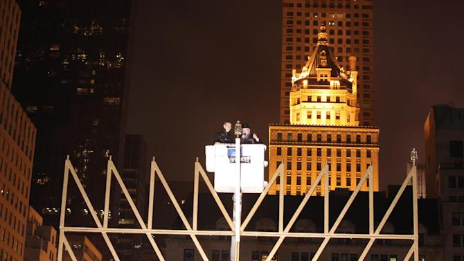 Rabbi Shmuel Butman, Director Lubavitch Youth Organization, right, and Tamir Sapir, head of the Sapir Organization in New York light the 32-foot-tall menorah that weighs about 4,000 pounds and has real oil lamps, protected from the wind by glass chimneys at the edge of Central Park, in New York, Saturday Dec. 8, 2012. (AP Photo/Lubavitch Youth Organization)