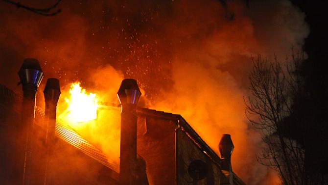 Flames rise at a house in Backnang, Germany Sunday March 10, 2013. An early-morning fire on Sunday at the  apartment building in southwestern Germany left seven people dead, six of them children, police said.  Authorities were alerted to the blaze in Backnang, a town near Stuttgart, at 4.30 a.m. Police said in a statement that they believe the fire broke out in a second-floor apartment, and said that their investigation is focusing on a heater in the apartment.  (AP Photo/dpa, Benjamin Beytekin)