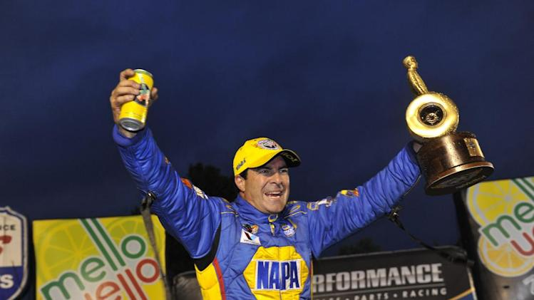 In this photo provided by the NHRA, Ron Capps celebrates winning the Brainerd Funny Car final held in Clermont, Ind., after the Brainerd finals were delayed due to rain, Saturday, Aug. 30, 2014. This is the second win of the season for Capps. (AP Photo/NHRA, Teresa Long)