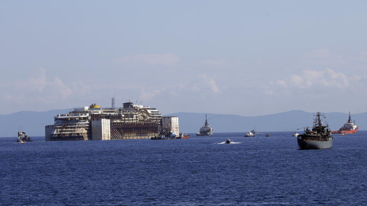 The Costa Concordia cruise ship, is towed away from the tiny Tuscan island of Isola del Giglio, Italy, Wednesday, July 23, 2014. (AP Photo/Gregorio Borgia)