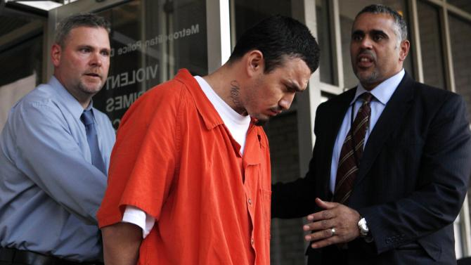 """FILE - In this April 22, 2009 file photo, 27-year-old Ingmar Guandique, center, accused of killing Washington intern Chandra Levy, is escorted from the Violent Crimes Unit in Washington by detectives Tom Williams, left, and Emilio Martinez. Levy vanished April 30, 2001 after completing a federal internship in Washington, and her remains were found in 2002 in a heavily wooded area of Washington's Rock Creek Park. Lawyers for Guandique, who was convicted of killing Levy, said in documents unsealed Tuesday, Feb. 19, 2013 that his prosecution was """"predicated on a lie,"""" and they intend to file a motion for a new trial. (AP Photo/Jacquelyn Martin, File)"""