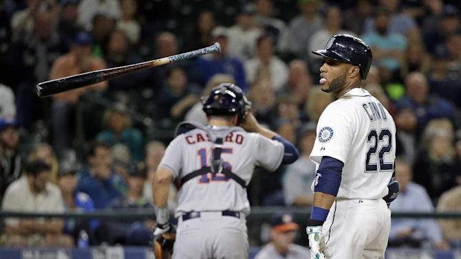 Seattle Mariners' Robinson Cano (22) tosses away his bat after striking out as Houston Astros catcher Jason Castro heads to his dugout in the sixth inning of a baseball game Monday, April 20, 2015, in Seattle. (AP Photo/Elaine Thompson)