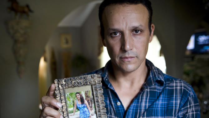 This Aug. 14, 2012 photo shows Rony Molina holding a photo of his wife in his home in Stamford, Conn. Molina's wife, Sandra Payes Chacon, was deported to Guatemala in 2010, leaving Molina alone to care for their three children, all American citizens. (AP Photo/Jessica Hill)